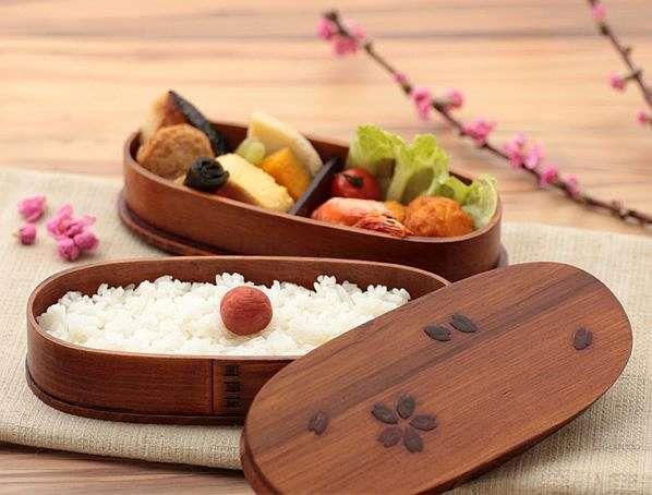日式木质便当盒,古朴的盒盖上是寥寥几笔的精美雕花,充满雅趣.